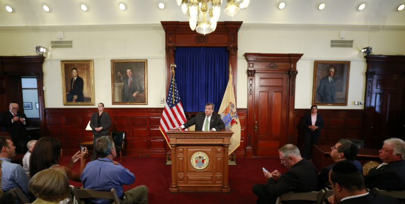 New Jersey Governor Chris Christie speaking at the bill signing ceremony of New Jersey's anti-BDS bill. Agudath Israel's New Jersey Director Rabbi Avi Schnall (bottom right corner) was one of several Jewish community leaders invited to the event.
