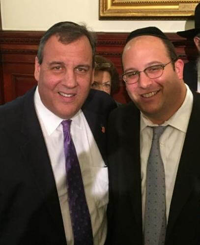 Rabbi Avi Schnall with New Jersey Governor Christie at the governor's Chanukah party